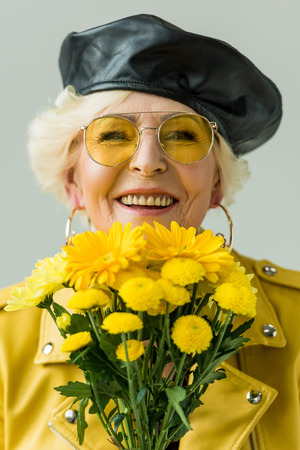 smiling senior woman in yellow leather jacket with bouquet of yellow flowers, isolated on grey Stock Photo