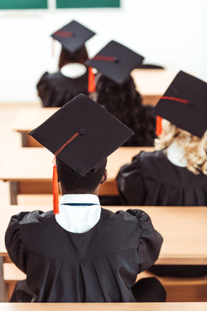 group of students in graduation hats sitting in class Stockfoto