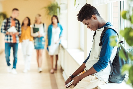 exhausted african american student sitting on windowsill