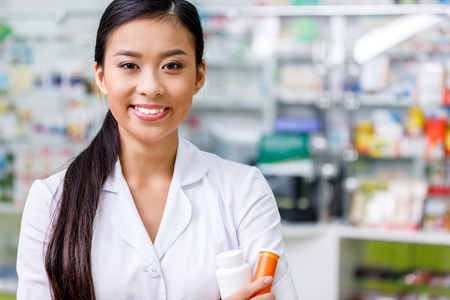 pharmacist in white coat holding containers with medication and smiling at camera 版權商用圖片
