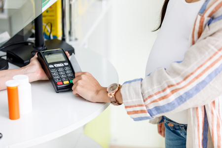 cropped shot of pregnant woman paying by credit card in drugstore