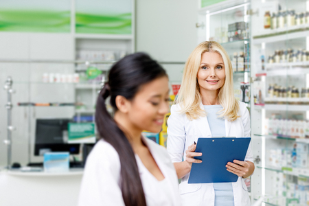 smiling female pharmacist in white coat holding clipboard and looking at asian colleague in drugstore