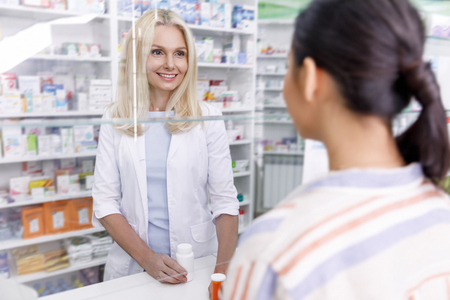 pharmacist and customer looking at each other in drugstore 免版税图像