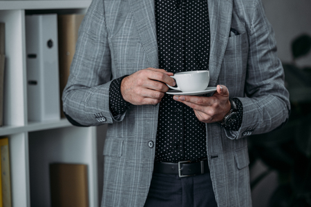 mid section of businessman holding cup of coffee and saucer in office Archivio Fotografico