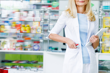 cropped shot of pharmacist holding digital tablet and putting pills into pocket of white coat 版權商用圖片