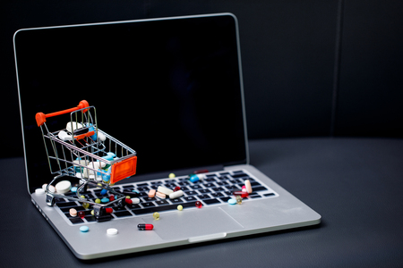 laptop with blank screen and pills in small shopping trolley