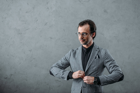handsome middle aged businessman buttoning suit jacket and looking away on grey