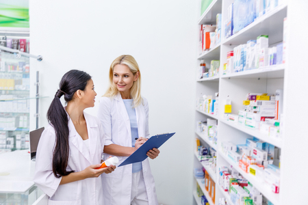 female pharmacists with medication and clipboard working together in drugstore