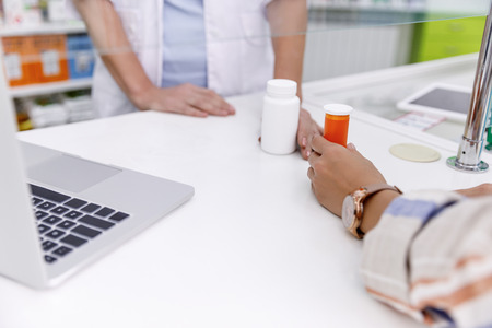 cropped shot of pharmacist giving containers with medication to customer in drugstore