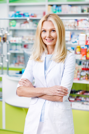 beautiful pharmacist in white coat standing with crossed arms and smiling at camera
