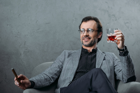 smiling middle aged businessman in eyeglasses smoking cigar and drinking whiskey