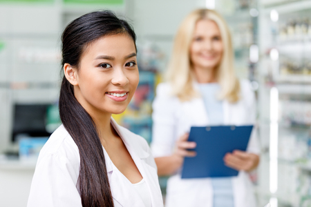 beautiful female asian pharmacist smiling at camera while colleague with clipboard standing behind