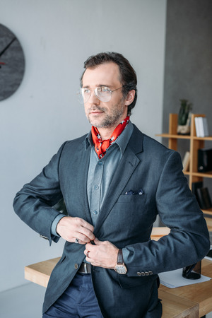 stylish businessman in eyeglasses buttoning suit jacket and looking away in office Stock Photo