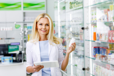 pharmacist with digital tablet and medication smiling at camera in drugstore 版權商用圖片