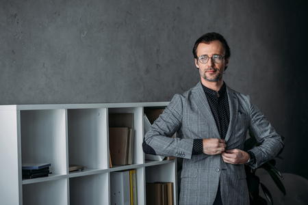 handsome middle aged businessman in eyeglasses buttoning suit jacket and looking away in office Stock Photo