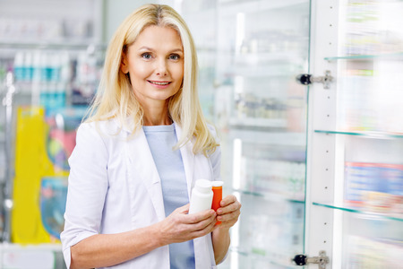female pharmacist holding containers with medications and smiling at camera 版權商用圖片