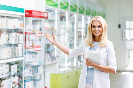 smiling female pharmacist holding digital tablet and showing medications in drugstore