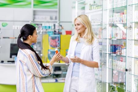smiling female pharmacist consulting customer in drugstore