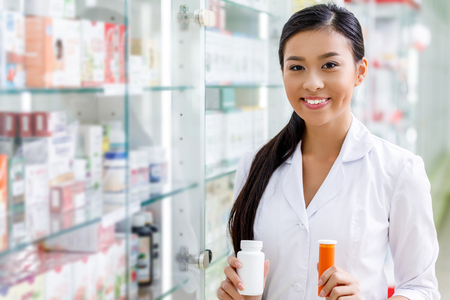 young pharmacist holding containers with medication and smiling at camera in drugstore Standard-Bild