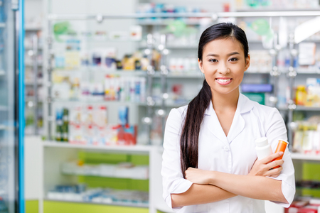 cheerful young asian pharmacist with medication smiling at camera in drugstore 版權商用圖片 - 102343346