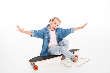 Excited child in oversized denim shirt sitting on a longboard, isolated on white