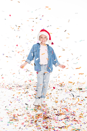 happy child in Santa hat with confetti on christmas, isolated on white