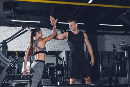 sportive couple giving high five to each other in gym