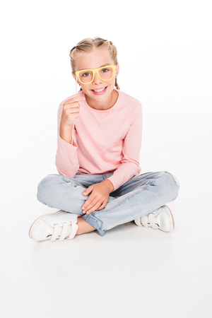 Cheerful child sitting on floor with legs crossed and playing with carnival cardboard glasses, isolated on white