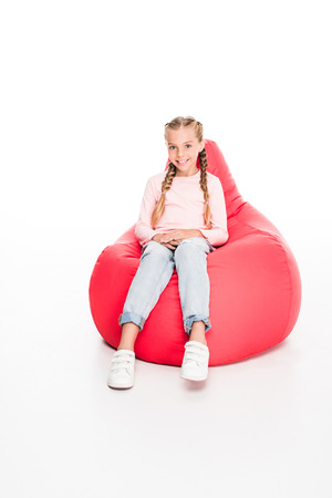 Young smiling child sitting on a red bean bag, isolated on white