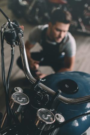 selective focus of classic motorbike in garage with repairman behind