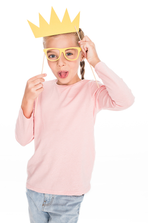 Mischievous child playing with cardboard masks and sticking tongue out, isolated on white
