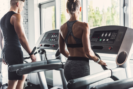 selective focus of couple exercising on treadmills in gym