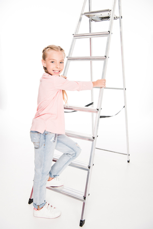 smiling kid climbing up the metal ladder, isolated on white Banque d'images - 102344775