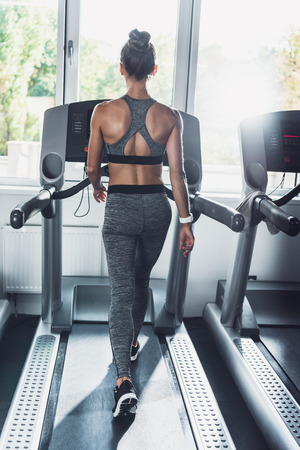 back view of woman doing cardio exercises on treadmill in gym Standard-Bild