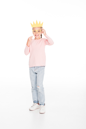 Smiling kid playing with carnival cardboard glasses and crown, isolated on white