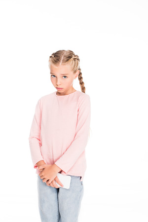 Young child holding smartphone with guilty look on her face, isolated on white