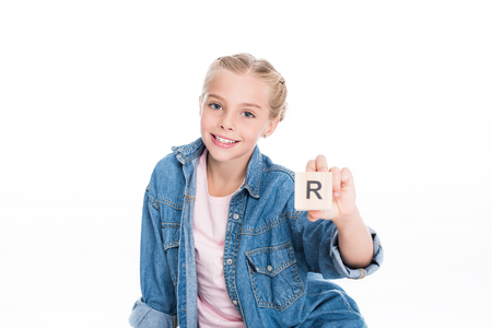Little child showing a letter cube with R engraved on it, isolated on white