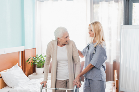 nurse and senior woman with walker smiling each other in hospital room