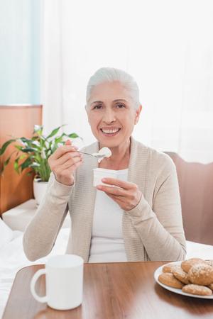 cheerful senior woman eating yogurt and smiling at camera