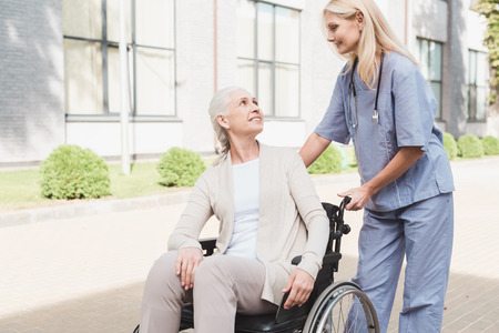 nurse and smiling senior patient in wheelchair smiling each other outside nursing home