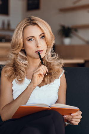 pensive blonde woman writing in notebook and looking away