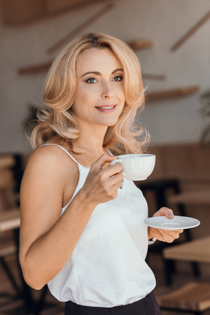 beautiful smiling middle aged woman holding cup of coffee and saucer