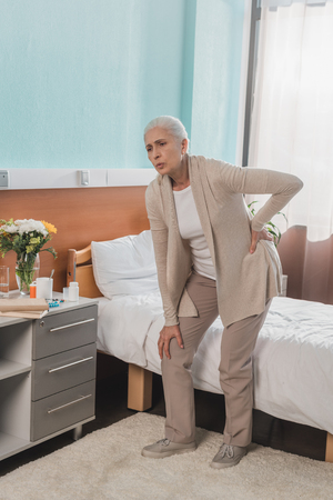 senior woman suffering from backache while standing in hospital room Stockfoto