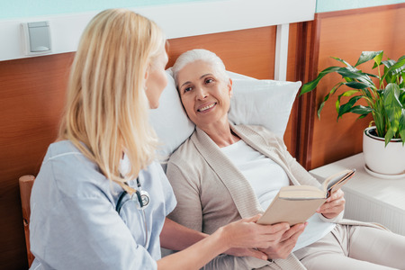 nurse and senior patient reading book and smiling each other at nursing home
