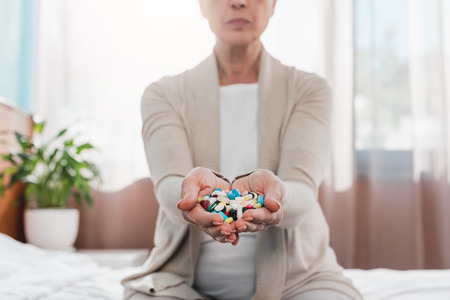 cropped shot of senior woman holding pills in hands