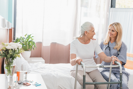 nurse and senior patient with walker smiling each other in hospital Banco de Imagens