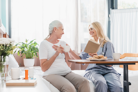 smiling senior woman and nurse reading book and drinking tea in hospital  Stock Photo
