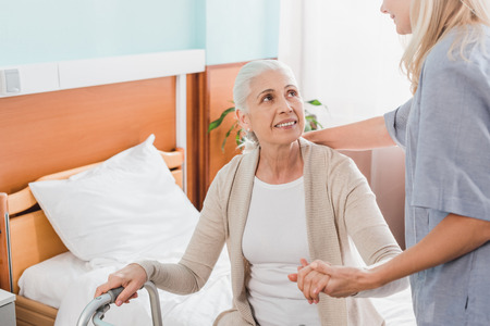cropped shot of nurse looking at senior woman with walker sitting on hospital bed Stok Fotoğraf - 102346175