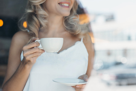 cropped shot of smiling blonde woman holding cup of coffee
