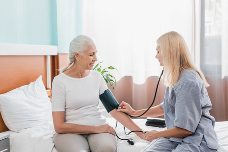 nurse measuring blood pressure to smiling senior woman in hospital